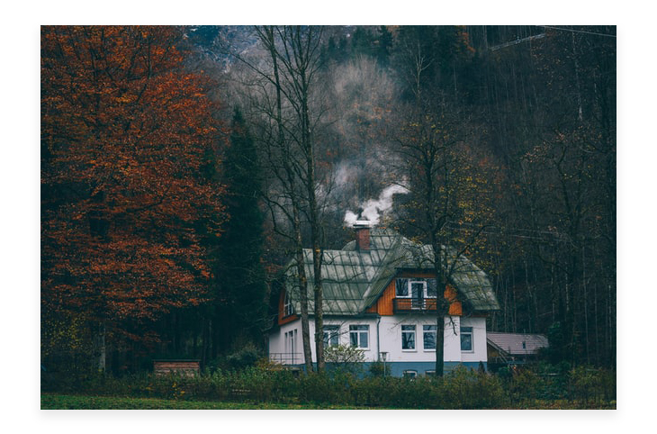 house with chimney located in the middle of the forest